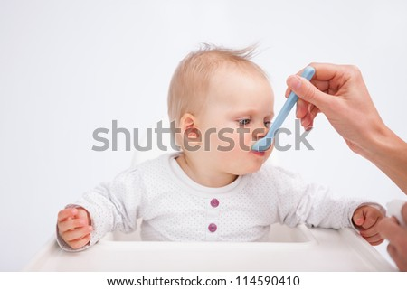 Cute baby eating while being accompanied by her mother against a grey background - stock photo