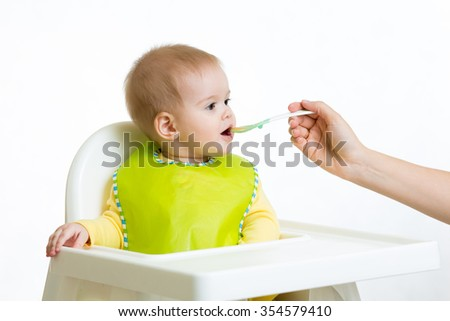 cute baby eats with spoon sitting in highchair - stock photo