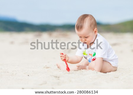 Cute baby exploring the sand on the beach with a toy shovel with mountains in the background