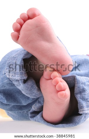 Cute baby feet in denim jeans.