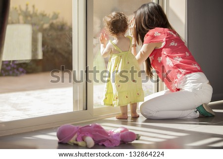 Cute baby girl and her mother looking outside through a glass door - stock photo