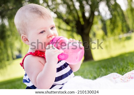 Cute baby girl celebrating 4th of July in the park. - stock photo