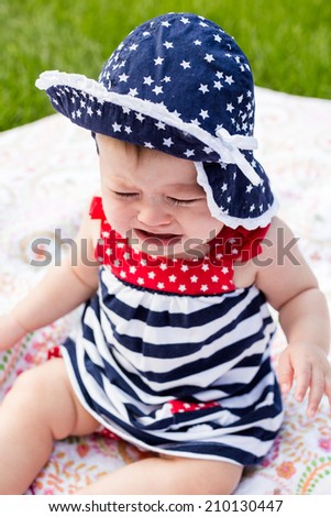 Cute baby girl celebrating 4th of July in the park.