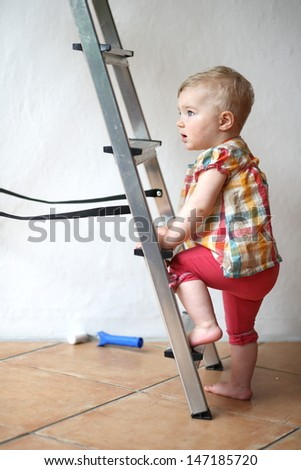 Cute baby girl climbing on a step ladder in domestic room during repair works