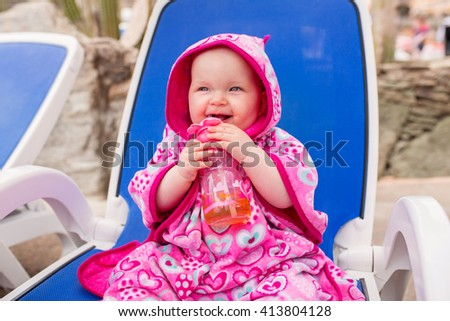 Cute baby girl covered by pink towel drinking juice at the pool