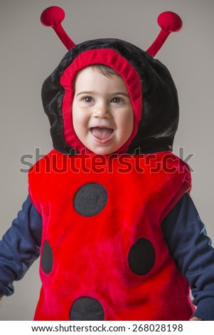 cute baby girl dressed in a beetle costume laughing - stock photo