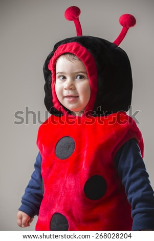 cute baby girl dressed in a beetle costume smiling - stock photo