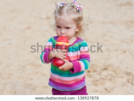 cute baby girl drinking from a bottle of red in nature - stock photo
