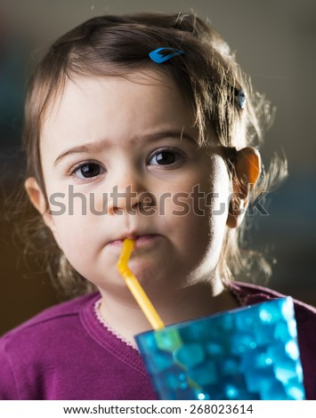 cute baby girl drinking with a straw - stock photo