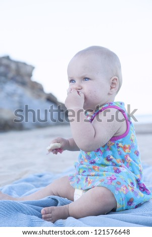 cute baby girl eating a snack (bread) on the beach. - stock photo
