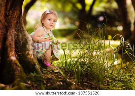 Cute baby girl eating apple under huge tree on green grass at sunny beautiful garden background - stock photo