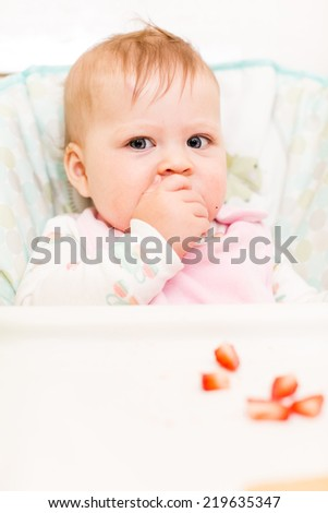 Cute baby girl eating meal in high chair.