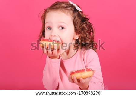 Cute baby girl eating sweet donuts over pink background - stock photo