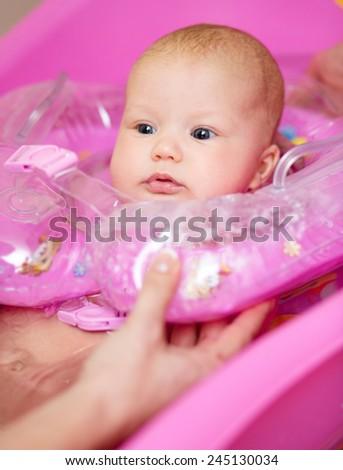 Cute baby girl enjoying bath, laughing while splashing water - stock photo