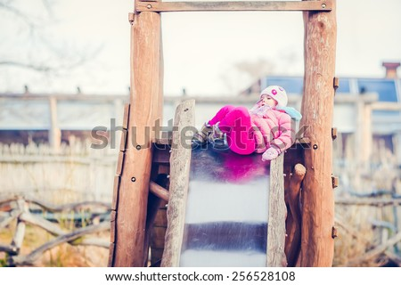 Cute Baby Girl Falls Down from a Playground Slide - stock photo
