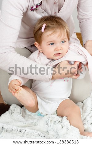 Cute baby girl getting dressed by mom while holding the foot with the hand
