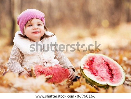 cute baby girl having a picnic, sitting on the grass in the autumn park and eating a long loaf - stock photo