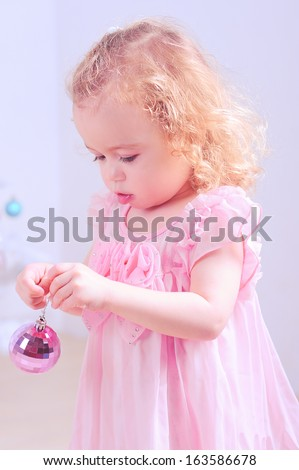 Cute baby girl holding pink christmas ball in room - stock photo