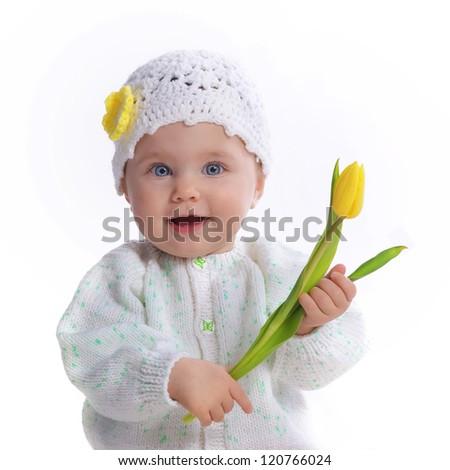 Cute baby girl holding yellow tulip - stock photo