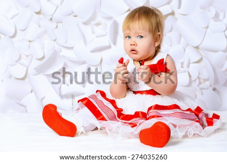 Cute baby girl in a beautiful dress on a background of white paper flowers. Childhood. Baby fashion. - stock photo