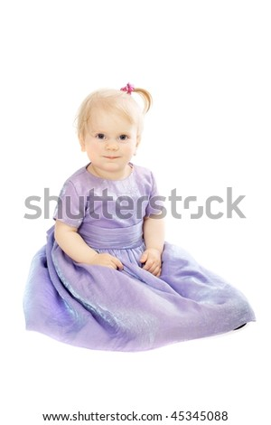 cute baby girl in a dress for the celebration smiling looking into the camera isolated on white