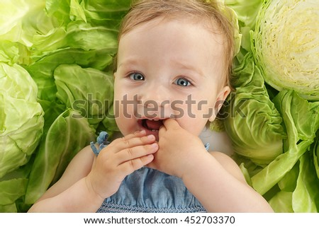Cute baby girl in cabbage, closeup - stock photo