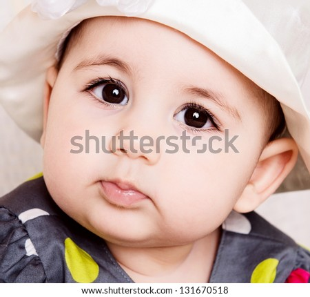 Cute baby girl in dotted dress in elegant hat - stock photo
