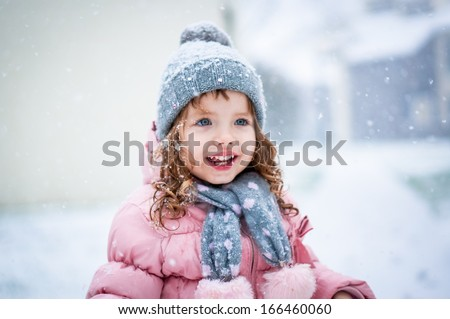 Cute baby girl in pink jacket and grey hat enjoying first snow blowing - stock photo