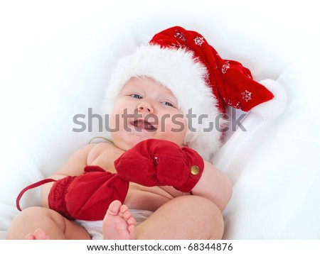 Cute baby girl in Santa hat and mittens