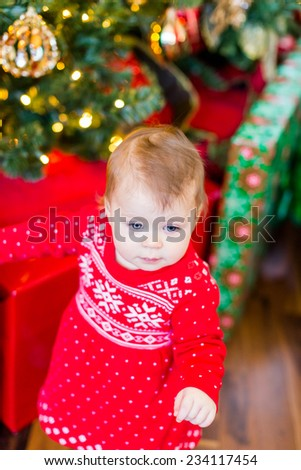 Cute baby girl in Scandinavian red dress next to Christmas tree.