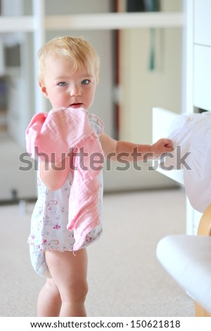 Cute baby girl in short dress and diaper stands in bedroom with big wardrobe and opens drawer of white commode to choose outfit - stock photo