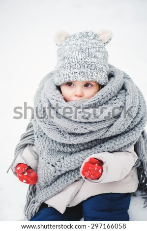 cute baby girl in snowy winter rolled up in oversize grey knitted scarf - stock photo