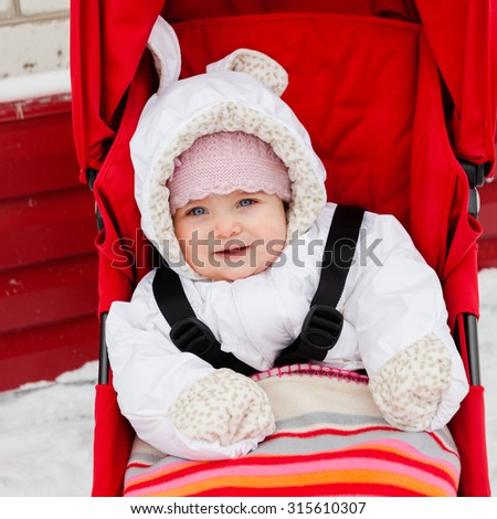 Cute baby girl in warm clothes and baby mittens sitting in stroller with fasten seat belts, covered with blanket. Snow and winter. Baby looking straight at the camera. Selective focus on baby head.