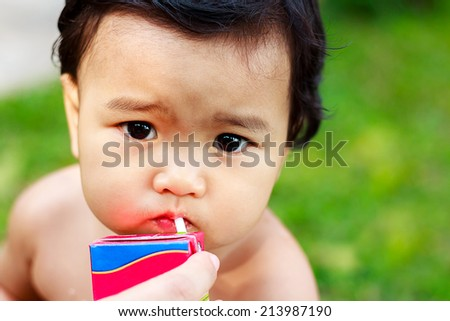 Cute baby girl is drinking milk using straw - stock photo