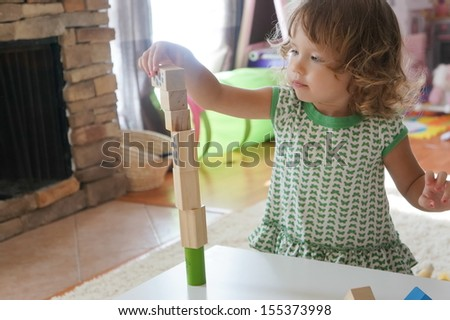 Cute baby girl is playing with wooden blocks