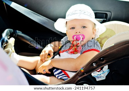 cute baby girl is sitting in car seat