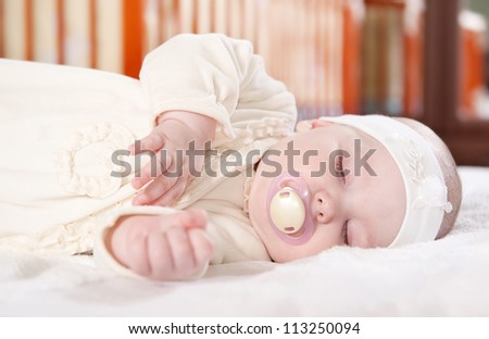 Cute baby girl is sleeping near her bed