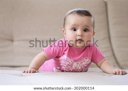 cute baby girl learning to crawl - stock photo