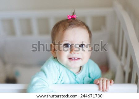 cute baby girl looking funny into the camera. Baby standing in the cot in the bedroom. - stock photo