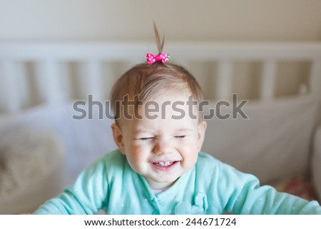 cute baby girl looking funny with closed eyes as wishing something. Baby standing in the cot in the bedroom. - stock photo