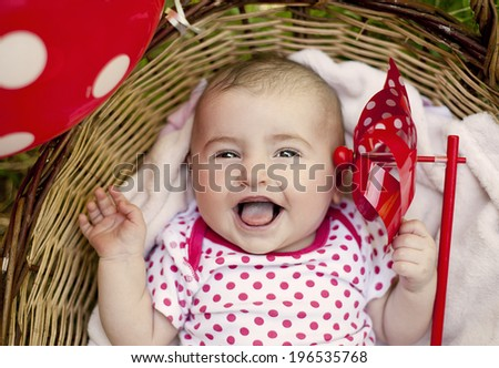 Cute baby girl lying down in basket in summer nature - stock photo