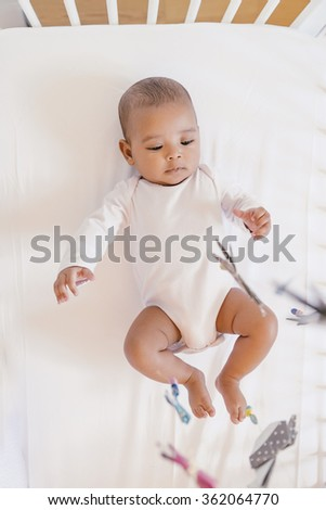 Cute Baby Girl Lying in the Crib. At home - stock photo