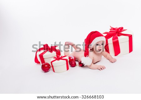 Cute baby girl lying naked on her stomach on a white background in a red New Year's cap among red Christmas balls and red boxes with gifts picture with depth of field