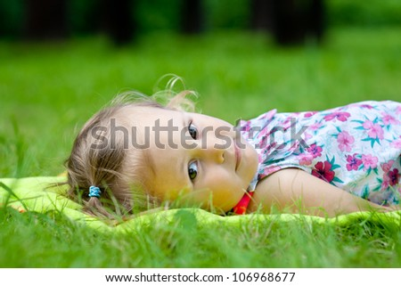Cute baby girl lying on grass