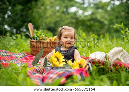 Cute baby girl on a picnic in nature, sitting on plaid blanket