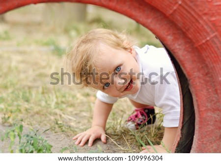 Cute baby girl peeping out of red tire in the playground - stock photo