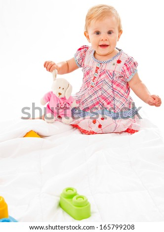 cute baby girl playing  on a white blanket with a rabbit and some building blocks