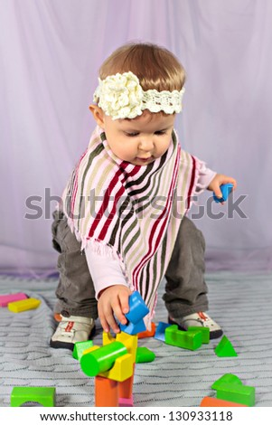 Cute baby girl playing with construction set - stock photo