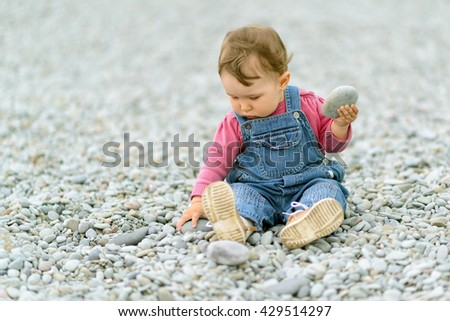 Cute baby girl playing with pebbles on the beach