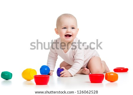 Cute baby girl playing with toys while sitting on floor, isolated over white - stock photo